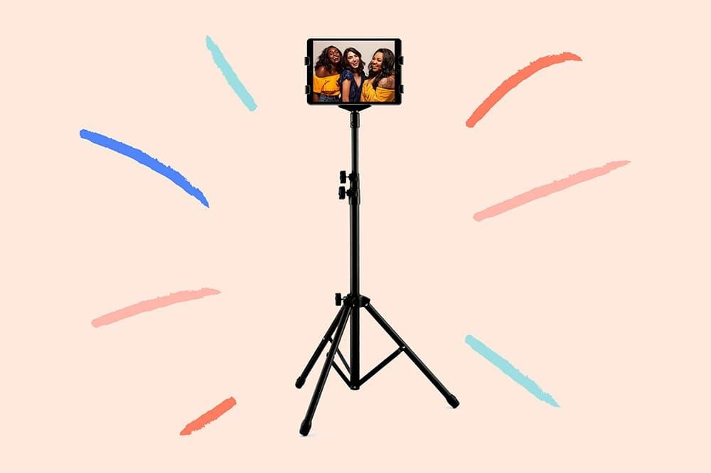 Le photobooth de Josepho est de face avec le message envoyé inscrit sur l'écran. Au premier plan une main tient un smartphone avec, sur son écran, la photo de deux amis prise avec le photobooth de Josepho.